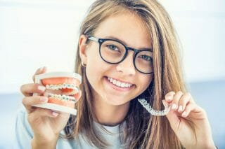 young girl holding up mold of braces