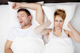 Woman trying to sleep while man snores beside her in bed
